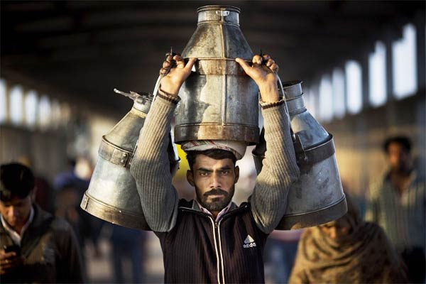 Indian Milkman Carries Milk Canisters