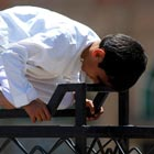 Young Boy Offering Prayer On A Fence