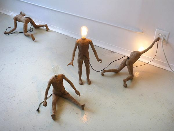 Miniature Lightbulb People Seek Life from Power Outlets