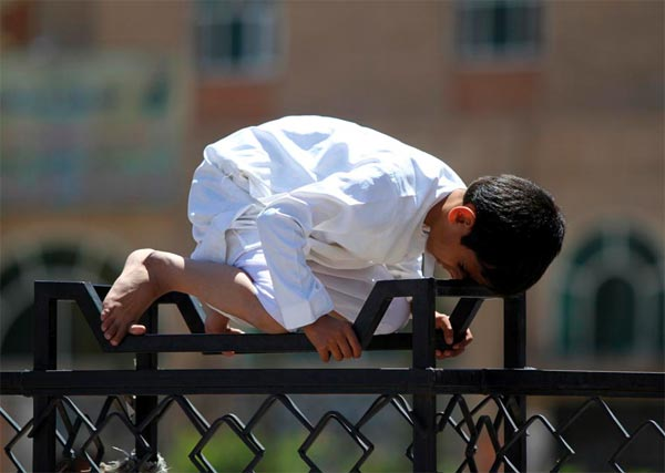 Boy Performing Prayer on Fence
