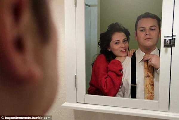 Dan Gregor & Rachel Bloom pose in a mirror while adjusting a loaf in supplement of his tie