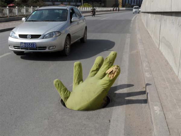 Giant green hand reaches out of manhole to remind drivers of danger