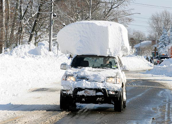Vehicle with a large chunk of snow on its top