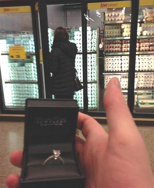 Man Taking Pictures with Engagement Ring and His Would-Be Fiance in the Background